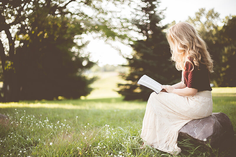 A woman sitting in the garden and reading a book